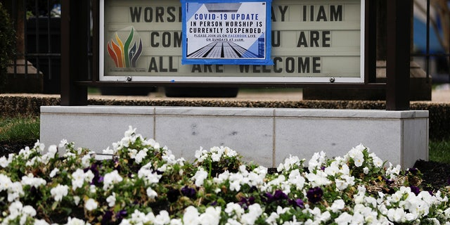 A sign displaying modified church services, due to the coronavirus disease (COVID-19) outbreak, is posted over a signboard outside Mount Vernon Place Methodist Church in the Mount Vernon neighborhood of Washington, U.S., March 19, 2020. REUTERS/Tom Brenner - RC27NF9YU070