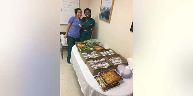 Health-care workers at NYU Langone Medical Center stand with donated meals from Tarallucci e Vino.