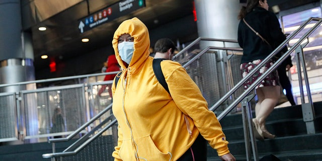 A commuter wears a face mask in the New York City transit system, Monday, March 9, 2020, in New York. New York continued grappling with the new coronavirus, as case numbers, school closings and other consequences grew.