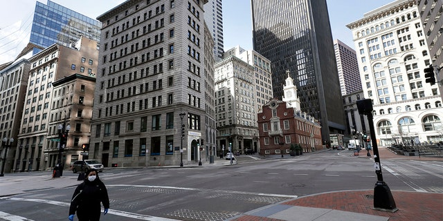 A passerby walks through a nearly empty intersection near the Old State House, center right, in downtown Boston, Tuesday, March 24, 2020. Many people are working from home in the state, while many businesses have closed indefinitely out of concern about the spread of the coronavirus. (AP Photo/Steven Senne)