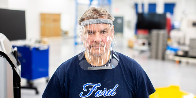 Dave Jacek, 3D printing technical, wears a prototype of a 3D-printed medical face shield printed at Ford's Advanced Manufacturing Center.