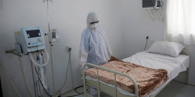 In this, Sunday, March 15, 2020 file photo, a medical staff member works on setting up an isolation room at a coronavirus quarantine ward at a hospital in Sanaa, Yemen.