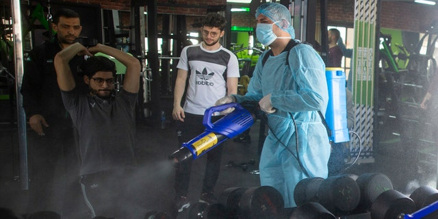 In this Sunday, March 15, 2020 file photo, a Palestinian health worker sprays disinfectant as a precaution against the coronavirus in a gymnasium in Gaza City.