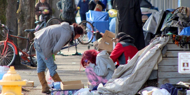 In this Tuesday, March 3, 2020 photo, homeless people crowd a sidewalk in downtown Salem, Ore., where they have set up a makeshift camp. Experts say that the homeless, who often have health and substance-abuse problems, are exposed to the elements and do not have easy access to hygiene, are more vulnerable to the coronavirus. Some cities are making provisions so the homeless who contract the virus have a place to recover without spreading the infection further. (AP Photo/Andrew Selsky)