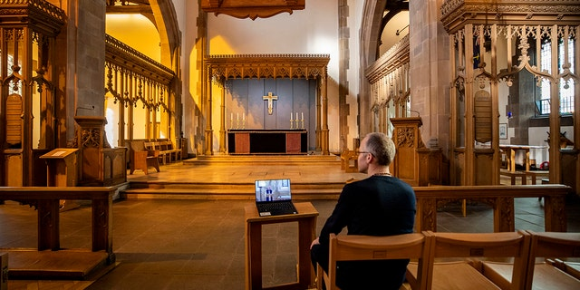 A church parishioner watches a laptop inside Liverpool Parish Church (Our Lady and St Nicholas) in Liverpool, England, during the Church of England's first virtual Sunday service given by the Archbishop of Canterbury Justin Welby. (Peter Byrne/PA via AP)