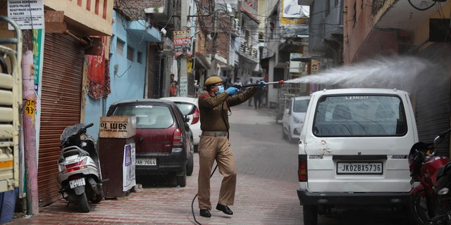 A fire brigade person disinfects an area during lockdown to prevent the spread of new coronavirus in Jammu, India, Tuesday, March 31, 2020.
