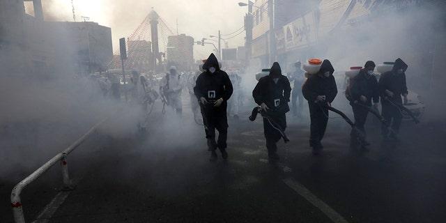 Firefighters disinfect a street against the new coronavirus in western Tehran on Friday. (AP Photo/Vahid Salemi)