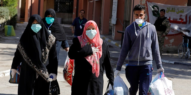 Iraqi women who have recovered from the coronavirus wear protective face masks as they leave the quarantine hospital, following the outbreak of the virus, in Baghdad, Iraq March 9, 2020.