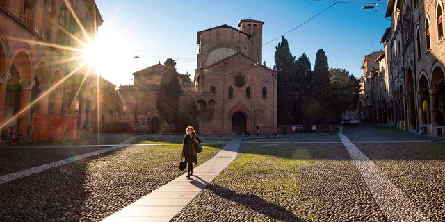 A woman walks past the Basilica of Santo Stefano, in Bologna on Wednesday following a country-wide lockdown. (Massimo Paolone/LaPresse via AP)
