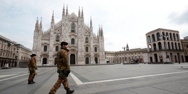 Italian soldiers patrol the square facing Duomo gothic cathedral in downtown Milan, Italy, Sunday, March 22, 2020. (AP Photo/Antonio Calanni)