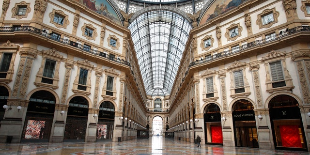 A man walks in an empty Vittorio Emanuele II gallery shopping arcade, in downtown Milan, Italy, Sunday, March 22, 2020.