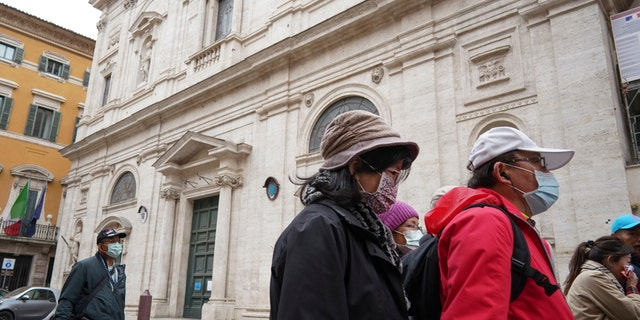 Tourists wearing protective masks walk past the St. Louis of the French church in Rome, Sunday, March 1, 2020.