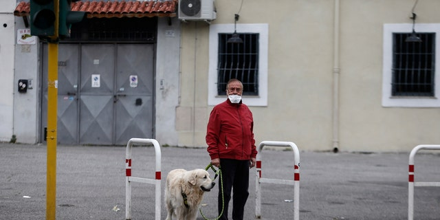 A man strolls with his dog in Rome Friday, March 13, 2020. A sweeping lockdown is in place in Italy to try to slow down the spread of coronavirus epidemic.