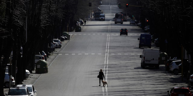 A woman walks her dog in the EUR neighborhood in Rome, Monday, March 23, 2020.