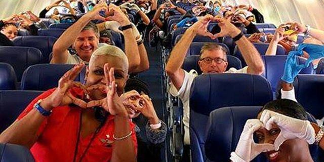 A spirited image of health care professionals, flight crew and passengers on a recent Southwest Airlines flight from Georgia, to help with the coronavirus outbreak in New York, has gone viral on social media.