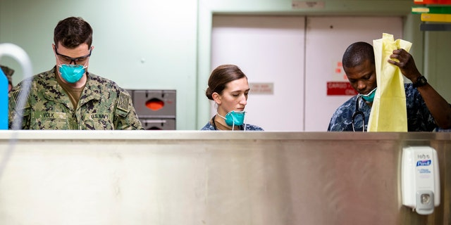 Sailors prepare for incoming patients aboard the hospital ship USNS Mercy March 29 in Los Angeles.