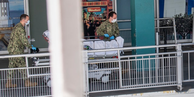 Sailors transport a patient to be admitted aboard the hospital ship USNS Mercy on Sunday, the first day the hospital ship saw patients while docked in Los Angeles..