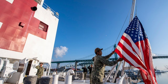Logistics Specialist 1st Class Tavares Littleton, from Chicago, raises the American flag during morning colors aboard the hospital ship USNS Mercy on Sunday in Los Angeles.