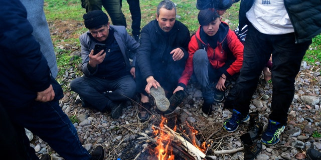 Migrants try to warm themselves around bonfire at the village of Skala Sikaminias, on the Greek island of Lesbos, after crossing on a dinghy the Aegean sea from Turkey, Sunday, March 1, 2020.