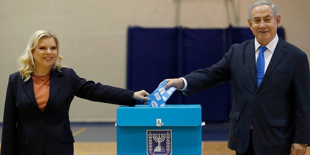 Netanyahu and his wife Sara cast their ballots during the Israeli legislative elections at a polling station in Jerusalem on Monday. (Atef Safadi/Pool Photo via AP)