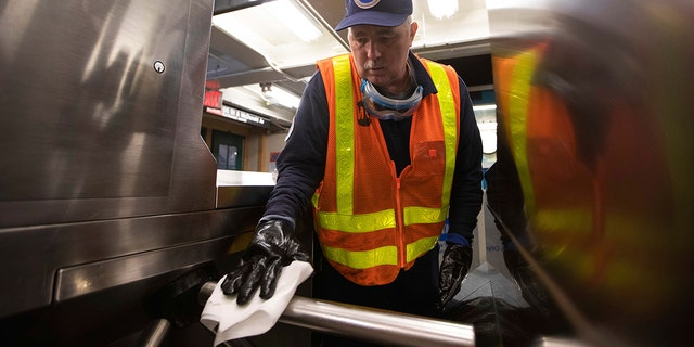 Worker Duane Clark works to sanitize surfaces at the Avenue X subway station on Tuesday in the Brooklyn borough of New York. (AP Photo/Kevin Hagen)