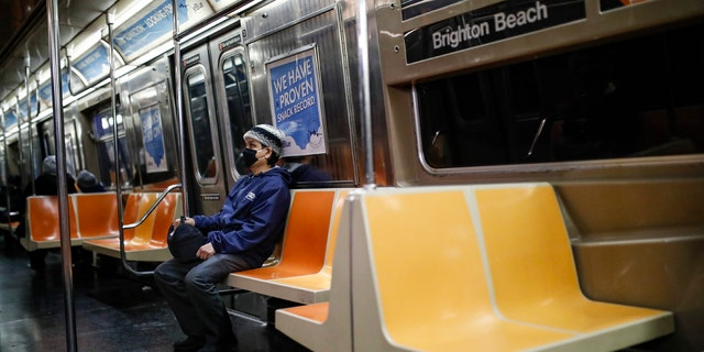 A commuter wears a face mask while riding the a nearly empty subway car into Brooklyn, Thursday, March 12, 2020, in New York. (AP Photo/John Minchillo)