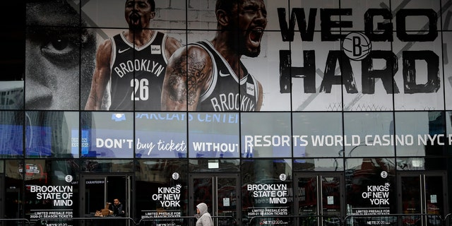A pedestrian passes an entrance to the Barclays Center in the Brooklyn borough of New York on Thursday, March 12, 2020, after the NCAA's Atlantic 10 Conference Tournament was announced cancelled due to concerns over the COVID-19 coronavirus. (AP Photo/John Minchillo)
