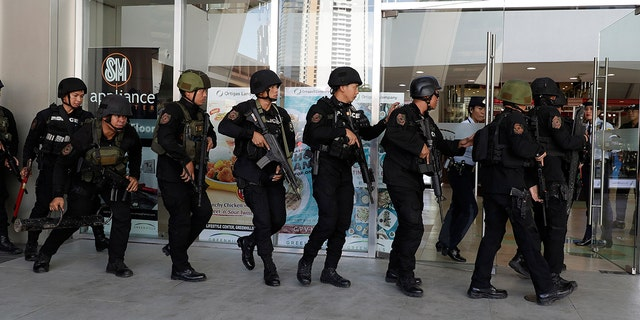 Philippine police on Monday surrounded the shopping mall in an upscale section of Manila after a recently dismissed security guard opened fire and took dozens of people hostage, an official said. (AP Photo/Aaron Favila)