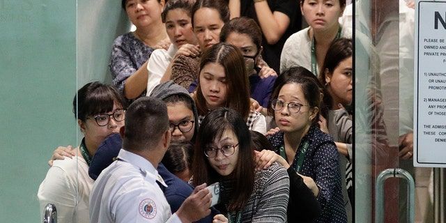 Hostages walk out of the V-Mall in Manila after a former security guard held them at gunpoint inside an office, officials said. (AP Photo/Aaron Favila)
