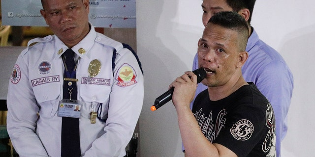 Former security guard Archie Paray, right, talks to media shortly after releasing all his hostages at the V-mall in Manila. (AP Photo/Aaron Favila)
