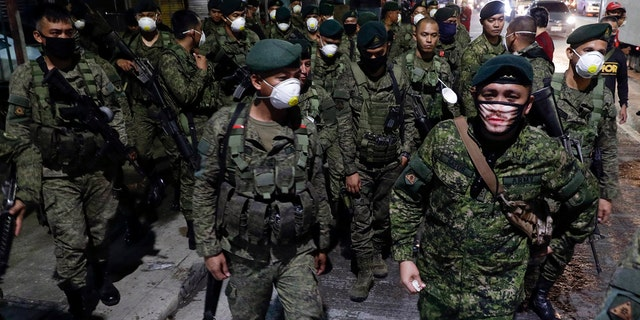 Thousands of Philippine police, backed by the army and coast guard, on Sunday worked to seal the densely populated capital, Manila, from most domestic travelers in one of Southeast Asia's most drastic containment moves against the coronavirus. (AP Photo/Aaron Favila)