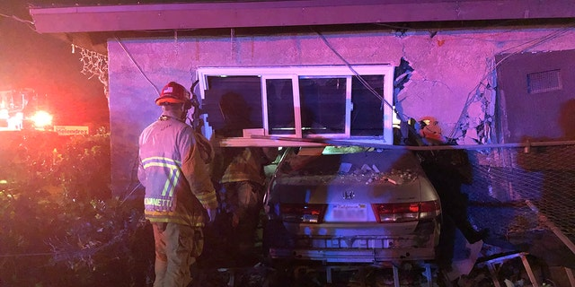 The car barreled into a home and almost completely entered the residence, where it pinned a sleeping man against a wall.