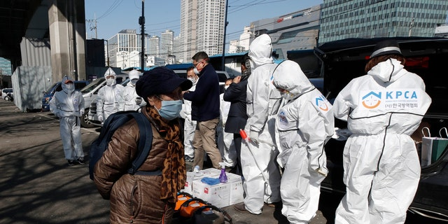 A woman wearing a face mask walks near workers wearing protective gears preparing to spray disinfectant as a precaution against the new coronavirus in Seoul, South Korea, on Monday.