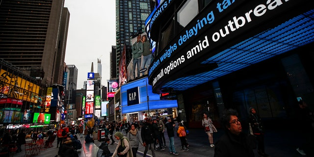 Pedestrians pass under a news ticker in Times Square, Wednesday, March 11, 2020, in New York, N.Y. The number of coronavirus cases in New York state jumped Sunday to more than 100, a spread that forced the suspension of classes at schools across the state, including a district that has a faculty member with a positive test and Columbia and Hofstra universities. For most people, the new coronavirus causes only mild or moderate symptoms. For some it can cause more severe illness.
