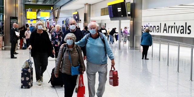Passengers from the coronavirus hit Braemar cruise ship return to Heathrow Airport in London, on Thursday, March 19, 2020.