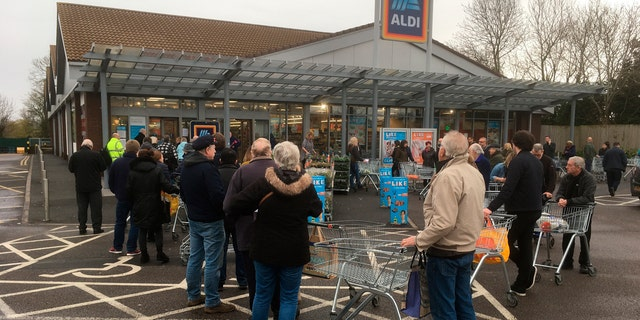 Early shoppers queue and wait in line for the opening of a supermarket in Rugby, England, Thursday, March 19, 2020.