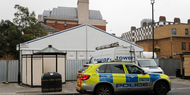 A police car in front of a tent being built to be used as a temporary morgue in London, Thursday, March 19, 2020.