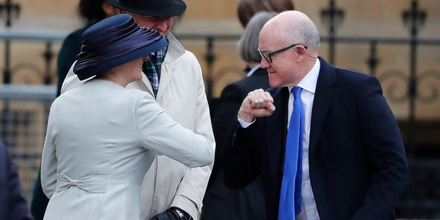 United States Ambassador to the United Kingdom Woody Johnson, right, greets by bumping elbows as he arrives to attend the annual Commonwealth Day service at Westminster Abbey in London on Monday. (AP Photo/Frank Augstein)