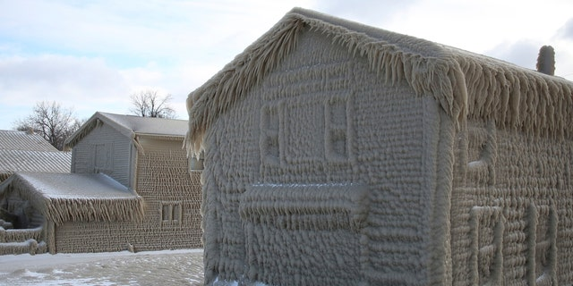 Houses along Hoover Beach is covered by ice from high winds and from the waves from Lake Erie, Saturday, Feb. 29, 2020, in Hamburg N.Y.