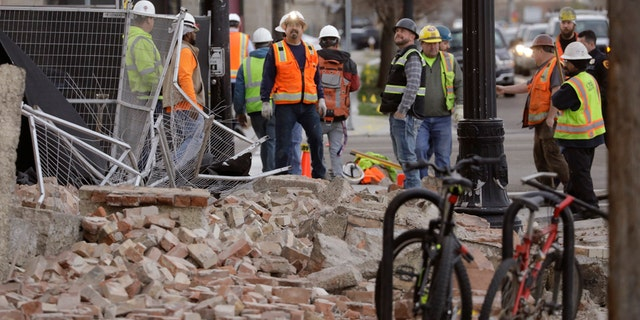 Construction workers looks at the rubble from a building after an earthquake Wednesday, March 18, 2020, in Salt Lake City.