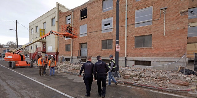 Police officers walk past rubble after an earthquake Wednesday, March 18, 2020, in Salt Lake City.