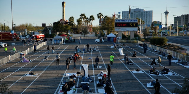 People prepare places to sleep at a makeshift camp for the homeless Monday, in Las Vegas.