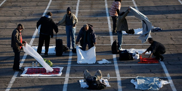 People prepare places to sleep in area marked by painted boxes on the ground of a parking lot at a makeshift camp for the homeless Monday, March 30, 2020, in Las Vegas.