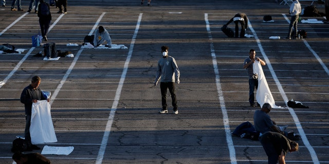 People prepare to sleep in areas marked by painted boxes on the ground of a parking lot at a makeshift camp for the homeless Monday, March 30, 2020, in Las Vegas.