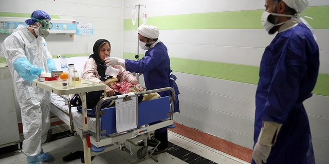In this Saturday, March 7, 2020 file photo, a cleric, right, assists a medic treating a patient infected with the new coronavirus, at a hospital in Qom, about 80 miles (125 kilometers) south of the capital Tehran, Iran.