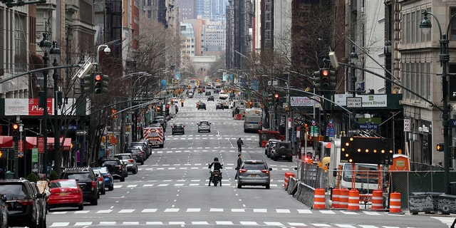 "Vehicles wait at stoplights on a virtually empty 5th Avenue on Sunday in New York City. The ""New York State on PAUSE"" executive order, a 10-point policy to assure uniform safety for everyone was implented Sunday. (Gary Hershorn/Getty Images)"