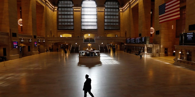 A train conductor walks through the virtually empty Grand Central Terminal on March 22, 2020, in New York City. (Photo by Gary Hershorn/Getty Images)