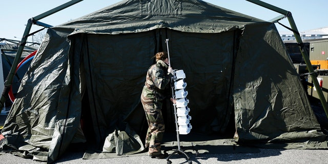 A French soldiers pulls medical gear at the military field hospital in Mulhouse on Tuesday after Macron ordered the facility built. (Mathieu Cugnot, Pool via AP)