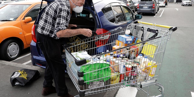 A man unpacks his shopping cart in a supermarket in central Christchurch, New Zealand in March. New Zealand's Prime Minister Jacinda Ardern announced that the country would go into full lockdown in about four weeks.