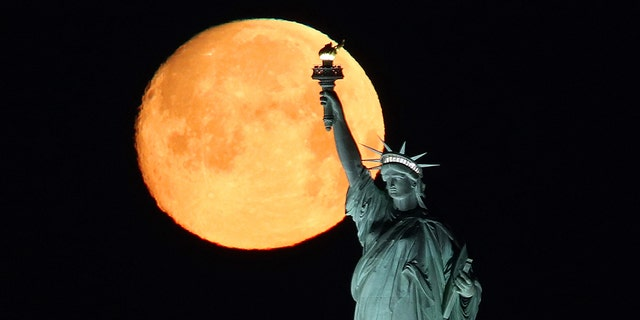 An almost full moon at 97.6 percent sets behind the Statue of Liberty on March 8, 2020 in New York City.